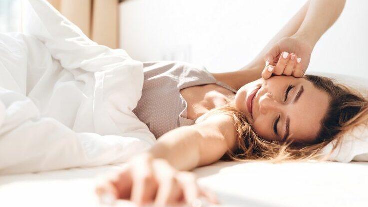 Žena v posteli se cítí dobře díky správné životosprávě